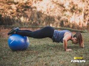 Imagem de jovem fazendo exercício físico no quintal com bola de pilates
