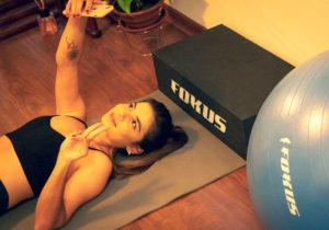 Imagem de mulher fazendo exercício físico ao lado de equipamentos fokus fit