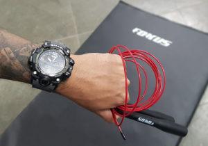 Imagem em destaque de mão masculina com relógio e corda de pular a frente de um tapete de exercícios fokus