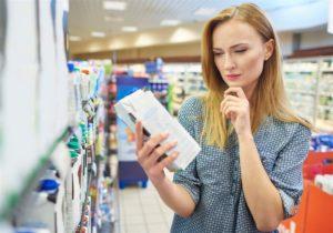 Imagem de uma mulher lendo o rótulo de uma embalagem em um supermercado